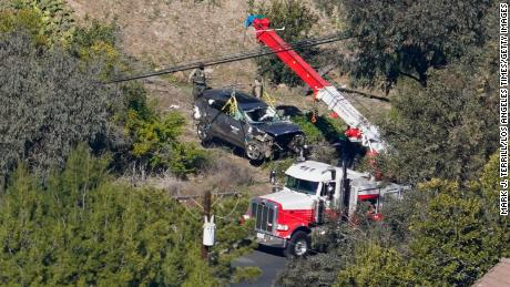 Workers move a vehicle after a rollover accident involving Tiger Woods on February 23, 2021