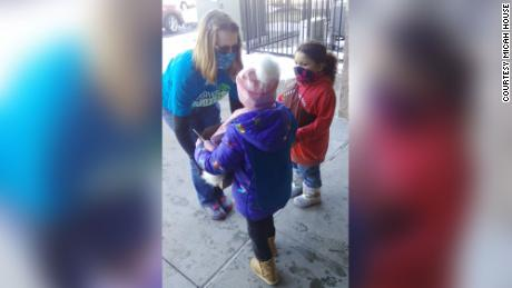 The Girl Scouts of Troop 64224 passing out boxes of cookies to a customer.