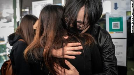 Mike Lam King-nam, who participated in the pro-democracy primary elections, gives a hug to his wife ahead of reporting the Ma On Shan Police Station on February 28,  in Hong Kong.