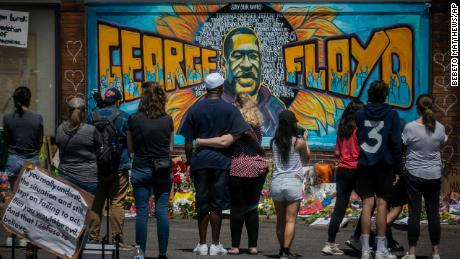 On May 31, mourners visit a memorial featuring a mural of George Floyd, near the spot where he died while in police custody.