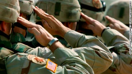 DUJAIL, IRAQ - OCTOBER 18:  U.S. Army soldiers salute during a memorial service for Sgt. Robert Tucker at a military base October 18, 2005 in Dujail, Iraq. Tucker, 20, from Cookeville, Tennessee, was killed by insurgents when a roadside bomb blew up his armored vehicle on October 13 near Dujail, just two weeks before the end of his 10-month deployment in Iraq. He was assigned to K-Troop, of the 278th Armored Cavalry Regiment, which patrols the area around Dujail. Saddam Hussein is scheduled to go on trial on October 19, for the death of 143 people from Dujail who he allegedly ordered killed in 1985 in revenge for an assassination attempt.  (Photo by John Moore/Getty Images)