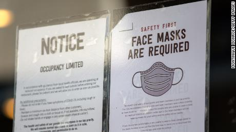 Signs about coronavirus restrictions hang outside of Chipotle in Austin, Texas on March 3, 2021.