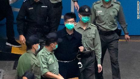 Aktivis Hong Kong Joshua Wong, salah satu dari 47 aktivis pro-demokrasi, dikawal oleh petugas Layanan Pemasyarakatan ke sebuah van penjara di Hong Kong pada hari Kamis.