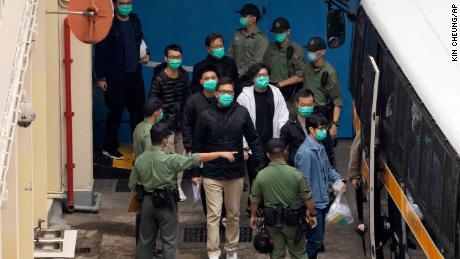 Beberapa dari 47 aktivis pro-demokrasi, termasuk Lam Cheuk-ting, tengah, dikawal oleh petugas Lembaga Pemasyarakatan ke sebuah van penjara pada hari Kamis.