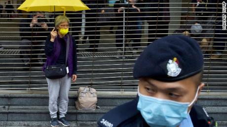 Seorang pendukung pro-demokrasi memegang payung antrian untuk sidang di luar gedung pengadilan di Hong Kong pada hari Kamis.