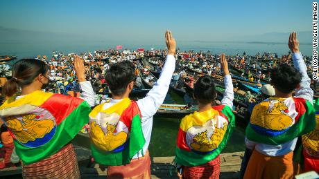 Protesters wearing traditional Shan dress make the three-figner salute as others hold signs during a demonstration against the Myanmar military coup in Inle lake, Shan state on February 11.