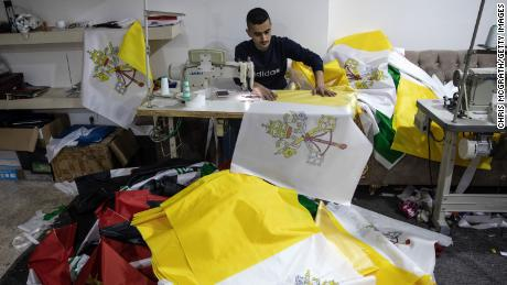 An employee works to sew the Vatican City flag at a printing house in Erbil, Iraq, on March 4.