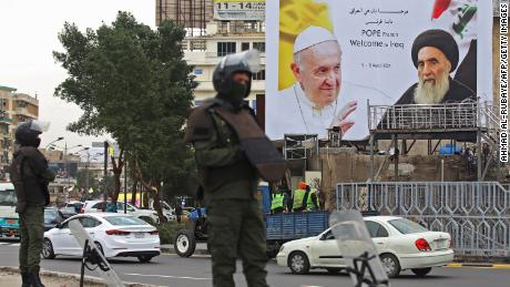 Iraqi security guards stand in front of a huge billboard bearing portraits of Pope Francis and Grand Ayatollah Ali al-Sistani in central Baghdad on March 4.