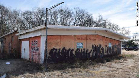 A former car dealership displays a graffiti representation of Bloody Sunday on its boarded facade.