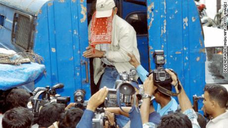 Sobhraj, face covered, is swarmed by photographers outside Kathmandu district court on September 22, 2003.