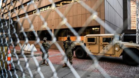 Members of the National Guard and Minnesota Police stand behind a barbed wire fence perimeter surrounding the Hennepin County Government Center on March 8, 2021 in Minneapolis, Minnesota.