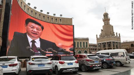 Vehicles stand in a parking lot as a large screen shows an image of Chinese President Xi Jinping in Kashgar, Xinjiang autonomous region, China, on Thursday, November 8, 2018.