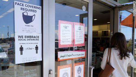A customer enters a store with a face mask required sign displayed on March 2, 2021, in Dallas
