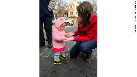 Clara, de 13 meses, toca curiosamente nas mãos da avó após meses de visitas atrás do vidro.