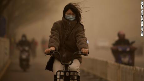 A woman cycles along a street during a sandstorm in Beijing on March 15.