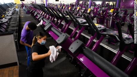 A Planet Fitness Inc. employee cleans gym equipment before the location's reopening after being closed due to Covid-19 on March 15, 2021 in Inglewood, Kalifornië.