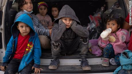 Asylum seeking migrant children from Central America take refuge from the rain in the back of a U.S. Border Patrol vehicle as they await to be transported after crossing the Rio Grande river into the United States from Mexico on a raft in Penitas, Texas, U.S., March 14, 2021. Pictured in the front row are Yoandri, 4, Michael, 5 and Yojanlee, 2, all from Honduras. REUTERS/Adrees Latif
