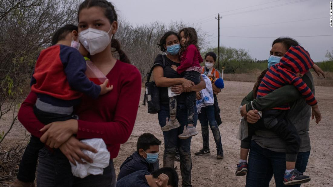 Migrant mothers from Central America hold their children as they await transport after crossing from Mexico into La Joya, Texas, en marzo 14.