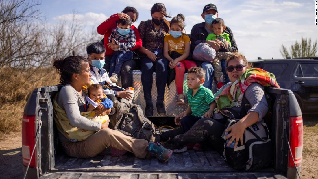 Migrant families and children sit in the back of a police truck after they crossed the Rio Grande on March 5.