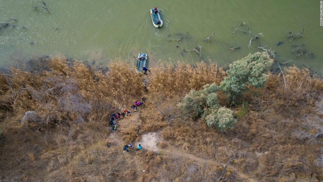 Migrants climb the banks of the Rio Grande into the United States as smugglers on rafts prepare to return to Mexico on March 5.