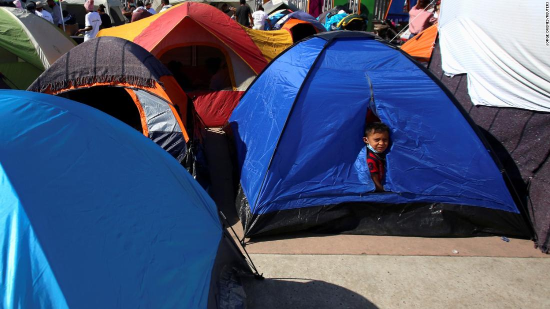 A child looks out from a tent in Tijuana, México, en febrero 27. Él's camped next to other migrants from Central America who are hoping to cross the border and request asylum in the United States.