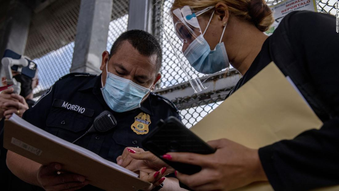 A US Customs and Border Protection officer checks for the name of a migrant as a group of at least 25 asylum seekers were allowed to travel from a migrant camp in Mexico into the United States on February 25. The group was the first allowed to cross into south Texas as part of the unwinding of the Trump administration's Migrant Protection Protocols. Many of the asylum seekers had been waiting in a squalid camp alongside the Rio Grande for more than a year.