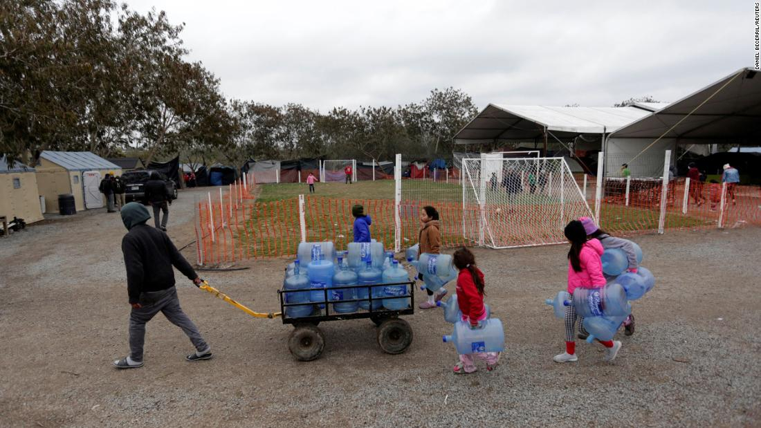 Migrants seeking asylum in the United States carry empty water jugs at a camp in Matamoros, México, en febrero 18.