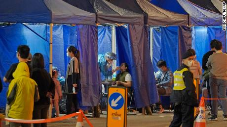 Government workers set up a temporary testing center for Covid-19 cordon outside an apartment block at Robinson Road in Hong Kong on Sunday.