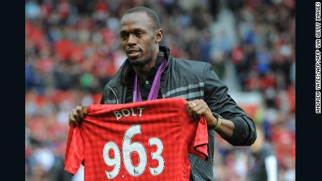 Usain Bolt on the pitch at Old Trafford with a United shirt displaying the time in which he won the 100m final at London 2012.