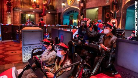 """In this picture taken on March 17, 2021, fans wear themed augmented reality goggles for the """"Mario Kart"""" ride at Super Nintendo World at Universal Studios Japan in Osaka."""