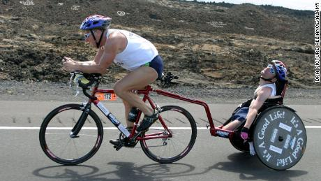 Dick Hoyt and his son, Rick, cross the lava desert during the cycling event of the 27th Iron Man competition in Kailua-Kona, Hawaii, on October18, 2003.