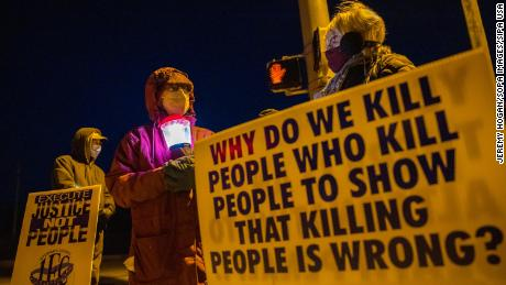 Bloomington anti-death-penalty activist Glenda Breeden holds a lamp while protesting against the execution of Lisa Montgomery, and two on January 12, 2021.