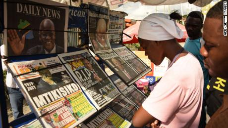 People read newspapers announcing the death of President John Magufuli in Dar es Salaam, Tanzania, on March 18, 2021.