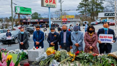 Members of the Atlanta Korean American Committee Against Asian Hate Crime hold a remembrance vigil at the scene of two of the massage parlor shootings in Atlanta.