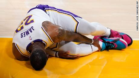 Los Angeles Lakers forward LeBron James holds his ankle after going down with an injury during the first half of a game against the Atlanta Hawks Saturday, March 20, 2021, in Los Angeles.