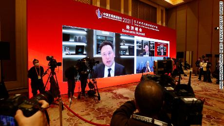 A screen showing Tesla CEO Elon Musk speaking via video link during the China Development Forum at Diaoyutai State Guesthouse on Saturday in Beijing.