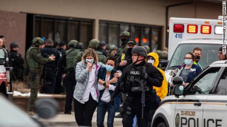 Health care workers walk out of a King Sooper's grocery store after a gunman opened fire in Boulder, Colorado, on Monday, March 22.