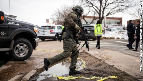 A SWAT team member runs toward the King Soopers grocery store where a gunman opened fire on Monday, March 22.