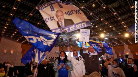 Likud supporters wave flags bearing the party name and the face of its leader, Benjamin Netanyahu, at its campaign headquarters in Jerusalem on March 23.