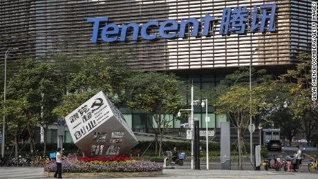 """A worker watering flowers around an installation reading """"Follow Our Party Start Your Business,"""" in front of Tencent's headquarters in Shenzhen, China in March."""