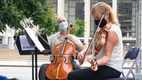 Principal Cello Carter Brey, and Principal Viola Cynthia Phelps of the New York Philharmonic perform a surprise free show outside Lincoln Center on July 7, 2020 in New York City. (Photo by Noam Galai/Getty Images)