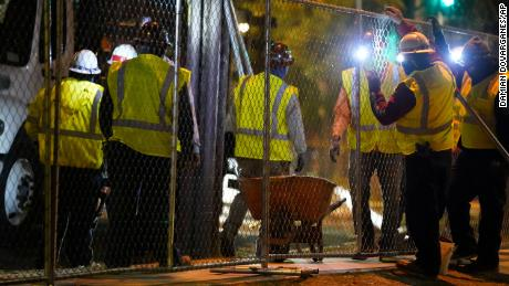 Contractors install a temporary fence around Echo Park Lake's perimeter in Los Angeles early Thursday.