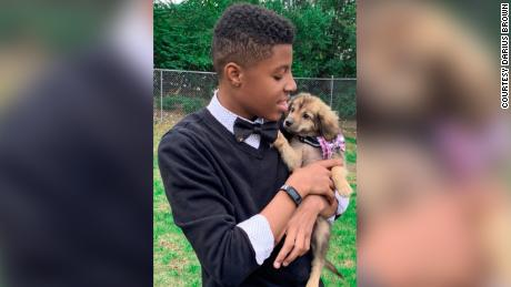 Darius Brown with a shelter dog that's wearing one of his bow ties.