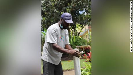 A contractor for CARE International fits taps onto new water pipes as part of the NGO's efforts to construct hand-washing facilities.