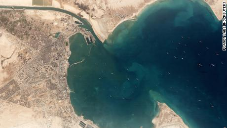 A satellite image shows the Ever Given and idling ships at the entrance of the Suez Canal.
