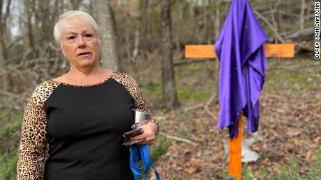 Dena Cook stands by the cross her husband built for her backyard.
