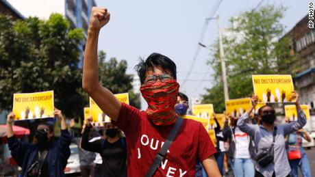 """Anti-coup protesters gesture during a march in Yangon, Myanmar, Friday, March 26, 2021. Protesters against last month's military takeover in Myanmar returned to the streets in large numbers Thursday, a day after staging a """"silence strike"""" in which people were urged to stay home and businesses to close for the day. (AP Photo)"""