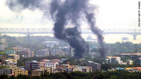 Smoke rises over Thaketa township in Yangon on March 27, 2021, as security forces continue their crackdown on protests against the military coup.