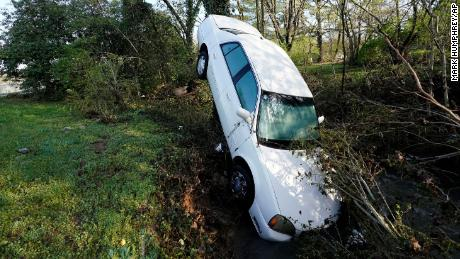 A car that was carried by floodwaters leans against a tree in a creek Sunday, Maart 28, 2021, in Nashville.