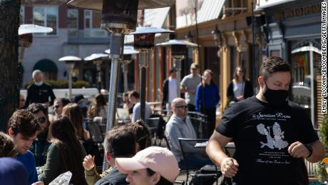 People dine outside at a restaurant in Plymouth, Michigan, on Sunday, March 21, 2021